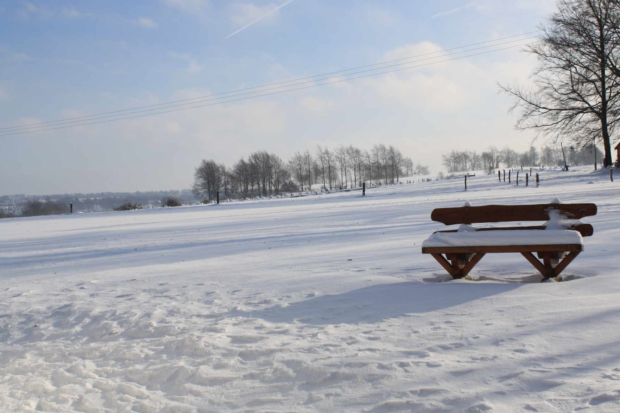 Schnee in Paustenbach (Eifel). Eine Bank in Schnee.